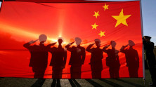 Retired paramilitary policemen, who conduct the daily national flag raising and lowering ceremony on Tiananmen Square, salute to a Chinese national flag
