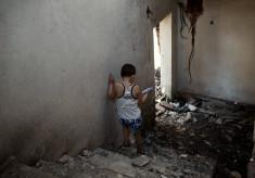 Mykyta walks down the staircase of his shelled apartment block near the village of Semenivka, near Sloviansk.