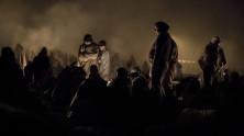 """Döda människor flyter iland på de grekiska och turkiska kusterna. Tusen och åter tusental kommer de, på flykt från krig och elände, """"med döden bakom mig och livet framför"""". Flyktingarna i Rigonce har kommit med tåg till en järnvägsstation på den kroatiska sidan av gränsen, därefter har de gått till fots en kilometer och anlänt hit till ett öppet vindpinat, stinkande fältet som är den första anhalten i Slovenien, porten mot Europa. Den nattliga väntan är kall och eländig och det många ännu inte är medvetna om är hur snabbt Europa vänder dem ryggen – att de har hamnat i ett humanitärt ingenmansland."""