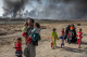 A family displaced by fighting in the village of Shora, 25 kilometres south of Mosul, walk towards an army checkpoint on the outskirts of Qayyarah. Liberated two months earlier, Qayyarah is still engulfed in thick black smoke from oil wells set ablaze by retreating militants. ; Around 3.3 million Iraqis, ten per cent of the population of Iraq, have fled their homes since fighting in several parts of the country intensified in March 2014. With a military operation to retake Mosul, Iraq's second largest city, beginning in October 2016, 11 new camps like the one in Jad'ah, Qayyarah, 80 kilometres south of Mosul, have been built by UN agencies and the Iraqi Ministry of Migration and Displacement. They are designed to accommodate 120,000 of the anticipated 1 million people likely to be displaced. It is one of 11 UNHCR camps planned to accommodate 120,000 displaced people. Emergency plans are also in place to provide tents and supplies to hundreds of thousands of people who cannot access the camps.
